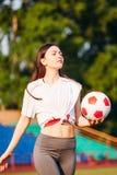 Jonge vrouw met voetbalbal in haar handen op voetbalgebied op achtergrond van tribunes royalty-vrije stock foto's