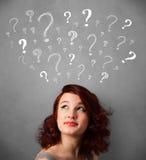 Jonge vrouw met vraagtekens boven haar hoofd Stock Foto
