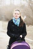 Jonge vrouw met wandelwagen Stock Afbeeldingen