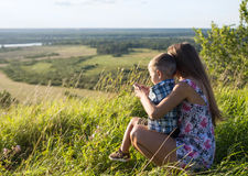 Jonge vrouw met weinig jongenszitting in hoog gras op heuvel Royalty-vrije Stock Afbeeldingen