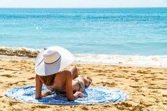 Jonge Vrouw met White Hat-het Ontspannen op Strand stock fotografie