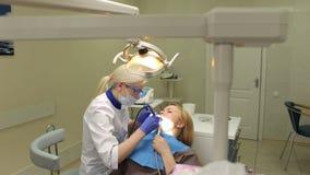 Jonge vrouw met witte tanden op tandarts` s kantoor stock video