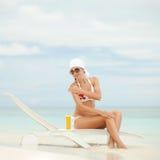 Vrouw met zon-bescherming room op het strand Stock Fotografie