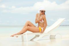 Vrouw met zon-bescherming room op het strand Stock Foto