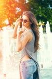 Jonge vrouw met zonnebril in de dag van de jeanszomer in stad stock foto's