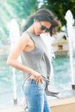 Jonge vrouw met zonnebril in de dag van de jeanszomer in de wind van het stads zijaanzicht in haar stock foto