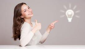 Jonge vrouw naast creativiteitsymbool Stock Foto