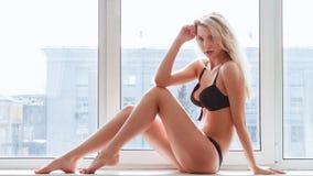 Jonge vrouw in ondergoedzitting op vensterbank Stock Afbeeldingen