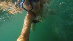 Jonge vrouw onderwater met zwemmend masker die aan actiecamera kijken en zonder aqualong in zeewater duiken stock video