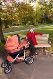 Jonge vrouw op bank met een kinderwagen Royalty-vrije Stock Foto's