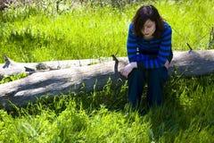 Jonge vrouw op boomstam Stock Afbeeldingen