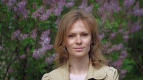 Jonge vrouw op de achtergrond van een lilac struik stock video