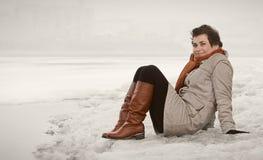 Jonge vrouw op de bank van de de winterrivier Stock Foto