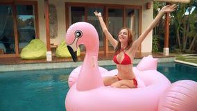 Jonge vrouw op de grote Vlotter van de Flamingo Opblaasbare Pool stock videobeelden