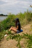 Jonge vrouw op de strandrivier die op de hengel kijken Stock Afbeelding