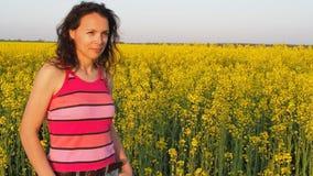Jonge vrouw op een gebied van gele bloemen Meisje in het platteland Een vrouw in een gestreepte T-shirt op een raapzaadgebied stock videobeelden
