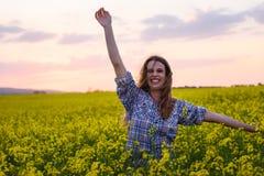 Jonge vrouw op een gebied van olieraapzaad in bloei in zonsondergang Vrijheid en ecologieconcept royalty-vrije stock foto's
