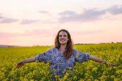 Jonge vrouw op een gebied van olieraapzaad in bloei in zonsondergang Vrijheid en ecologieconcept stock foto