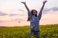 Jonge vrouw op een gebied van olieraapzaad in bloei in zonsondergang Vrijheid en ecologieconcept stock foto's