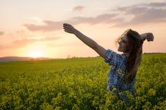 Jonge vrouw op een gebied van olieraapzaad in bloei in zonsondergang Vrijheid en ecologieconcept stock afbeelding