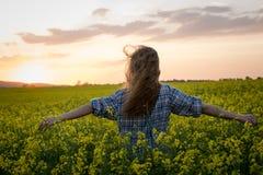 Jonge vrouw op een gebied van olieraapzaad in bloei in zonsondergang Vrijheid en ecologieconcept royalty-vrije stock fotografie