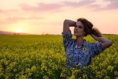 Jonge vrouw op een gebied van olieraapzaad in bloei in zonsondergang Vrijheid en ecologieconcept stock afbeeldingen
