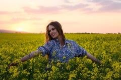Jonge vrouw op een gebied van olieraapzaad in bloei in zonsondergang Vrijheid en ecologieconcept royalty-vrije stock foto