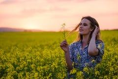 Jonge vrouw op een gebied van olieraapzaad in bloei in zonsondergang Vrijheid en ecologieconcept royalty-vrije stock afbeelding