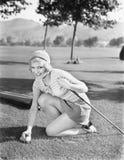 Jonge vrouw op een golfcursus die een golfbal plaatsen (Alle afgeschilderde personen leven niet langer en geen landgoed bestaat L Stock Fotografie