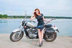 jonge vrouw op een motorfiets stock afbeelding