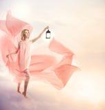 Jonge vrouw op fantasiewolken met antieke lamp Stock Afbeeldingen