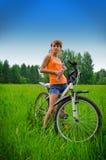 Jonge vrouw op fiets drinkwater Stock Afbeeldingen