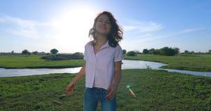 Jonge vrouw op groen grasgebied met rivier stock videobeelden