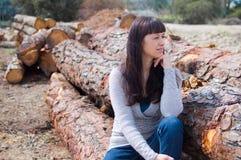 Jonge vrouw op het gestapelde hout Stock Afbeelding
