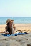 Jonge Vrouw op het Strand die Straw Hat dragen Royalty-vrije Stock Afbeelding