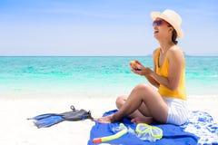 Jonge vrouw op het strand die zonroom toepassen royalty-vrije stock afbeeldingen
