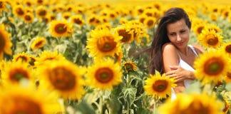 Jonge vrouw op het zonnebloemgebied Stock Afbeeldingen