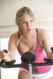 Jonge vrouw op hometrainer Stock Foto's
