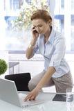 Jonge vrouw op mobiel in bureau Stock Foto