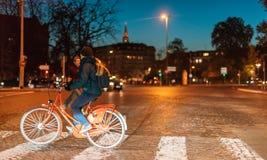 Jonge vrouw op rode ike die straat kruisen bij nacht voor Stock Foto's