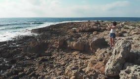 Jonge vrouw op rotsen die beelden met camera nemen Sterke overzeese oceaangolven die kustlijn raken Luchthommelmening Zonsonderga stock video