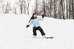 Jonge vrouw op snowboard Royalty-vrije Stock Afbeelding