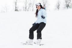 Jonge vrouw op snowboard Stock Afbeeldingen