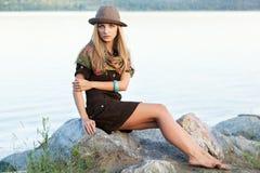 Jonge vrouw op stenen dichtbij water Royalty-vrije Stock Foto's