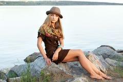 Jonge vrouw op stenen dichtbij water Stock Foto