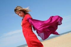 Jonge vrouw op strand met rode fladderende sjaal stock fotografie