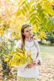 Jonge vrouw in openlucht in park op zonnige de herfstdag royalty-vrije stock afbeeldingen