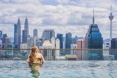 Jonge vrouw in openlucht zwembad met stadsmening in blauwe hemel royalty-vrije stock foto's
