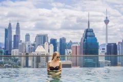 Jonge vrouw in openlucht zwembad met stadsmening in blauwe hemel royalty-vrije stock fotografie