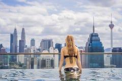 Jonge vrouw in openlucht zwembad met stadsmening in blauwe hemel Rijken royalty-vrije stock afbeelding